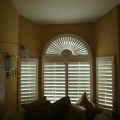 sunburst-arch-shutter-over-plantation-shutters