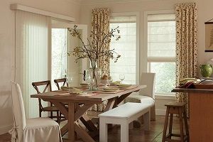 Multi-layered window treatments of draperies paired with shades in the dining area of a kitchen.