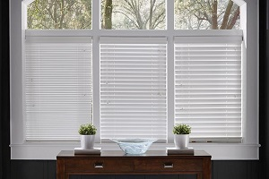 One large window split into three plains, where each plain has different sized, white blinds.