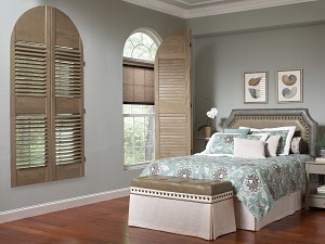 Window shutters matching the teal and light brown bedspread in a bedroom.