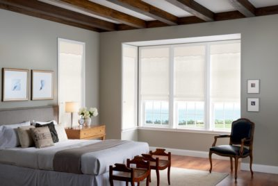 Partially sheer white shades half open on three vertical windows in a bedroom.