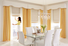 woman adjusting draperies in dining room