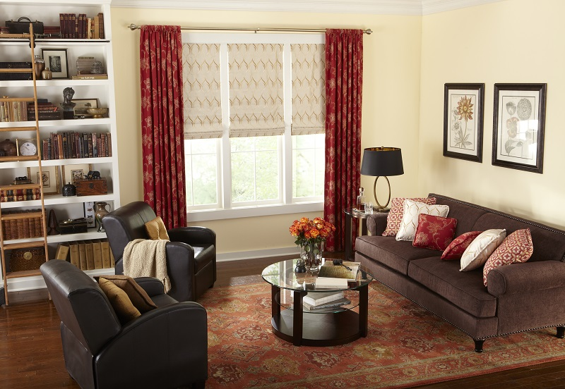 Layered roman shades paired with red drapery panels in a gorgeous living room.