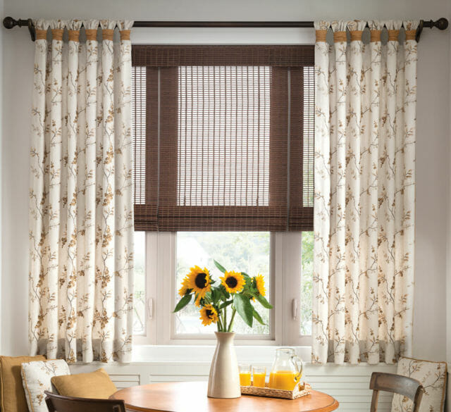 Fabric drapes create contrast with woven wood shades