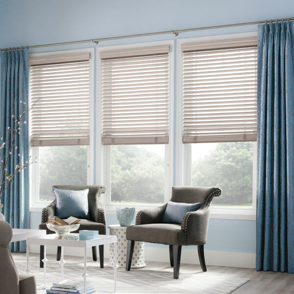 Curtains are layered over horizontal blinds